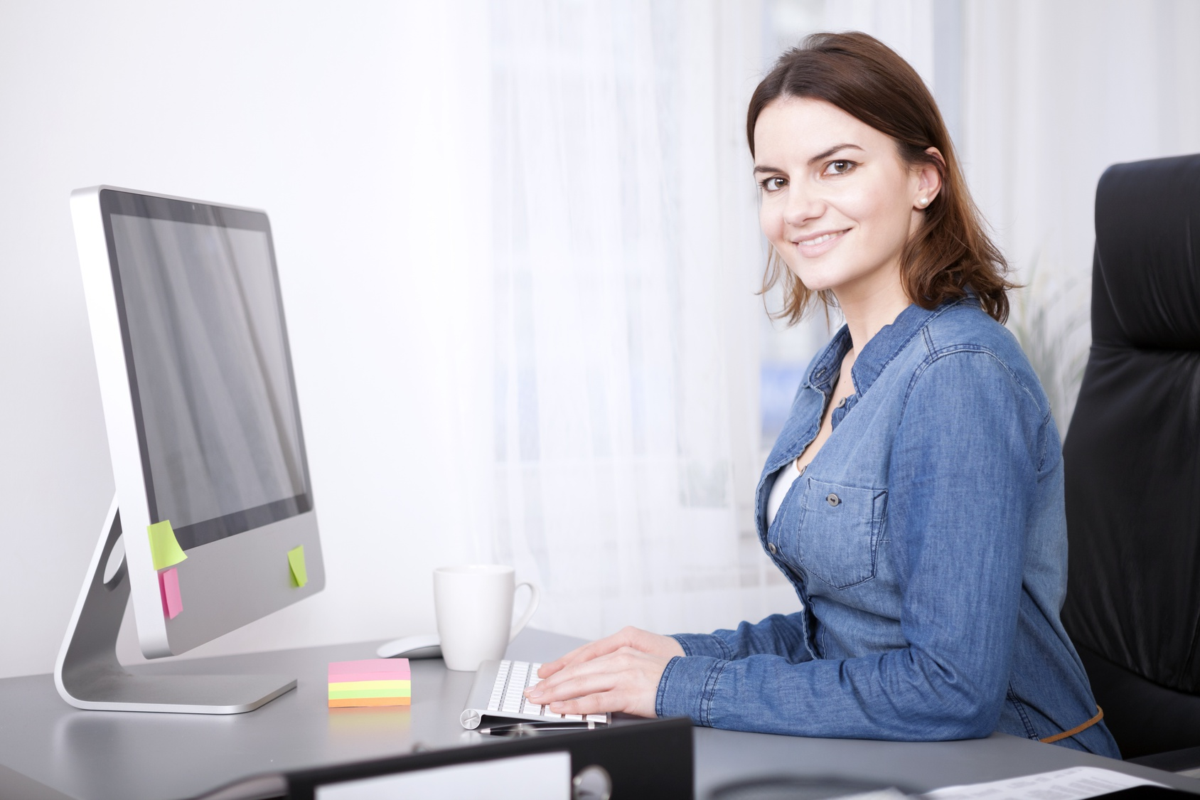 Attractive successful confident manageress working at her desktop computer in the office turning to smile at the camera, side view
