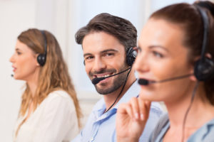 Portrait of happy telephone operator smiling. Joyful agent working in a call centre with his colleaugues in a row. Close up of happy telephone operators working in a row.